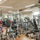 Fitnessstudio mit zahlreichen Geräten und Hanteln